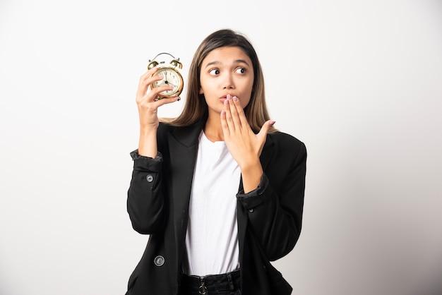 Femme d'affaires tenant un réveil sur un mur blanc.