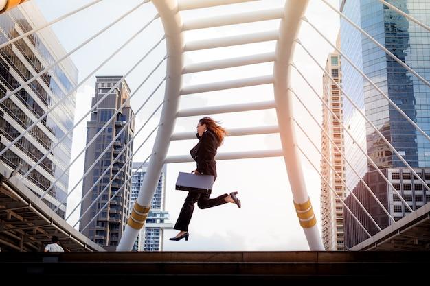 Femme d'affaires tenant le sac et sauter par-dessus l'escalier dans la pose de gagnant. dans l'heure de pointe dans la ville.
