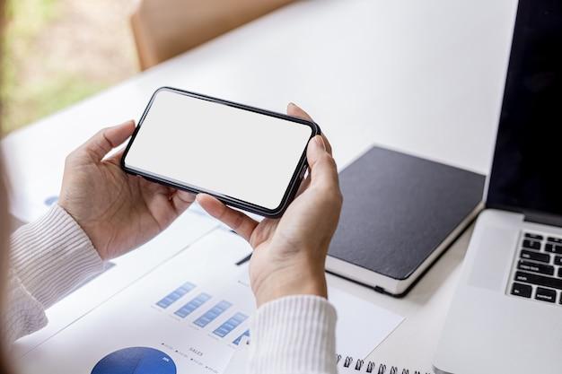Femme d'affaires tenant un smartphone sur un bureau avec des documents et un ordinateur portable placés, elle regarde les données du téléphone portable, l'écran vide du téléphone portable pour les graphiques publicitaires. le concept d'utilisation de la technologie