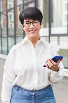 Femme d'affaires tenant son téléphone portable et sourit