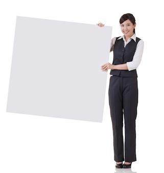 Femme d'affaires tenant un tableau blanc sur fond blanc.