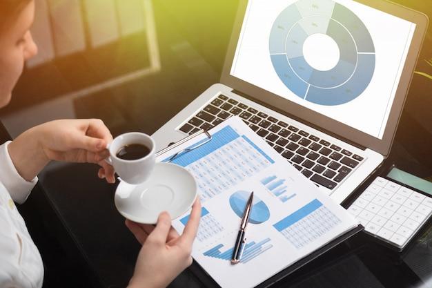 Femme d'affaires tenant une tasse de café et familiariser avec les diagrammes