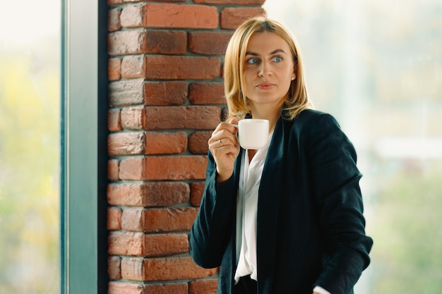 Femme d'affaires tenant une tasse de café à la recherche sur le côté. jeune blonde élégante debout près de la fenêtre du bureau. profitez d'un café pendant votre pause de travail.