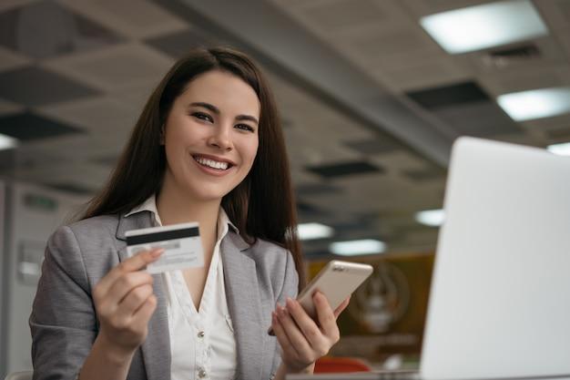 Femme affaires, tenue, carte de débit, utilisation, smartphone, achats en ligne, séance, dans, bureau