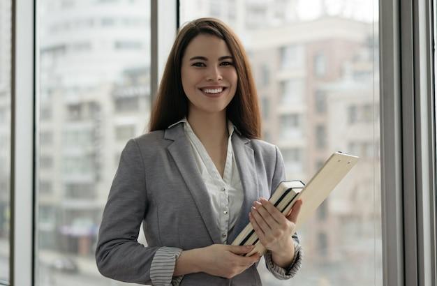 Femme affaires, tenue, documents, livres, debout, bureau, fenêtre