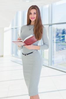 Femme affaires, tenue, a, journal intime, dans, elle, mains, et, regarder appareil-photo
