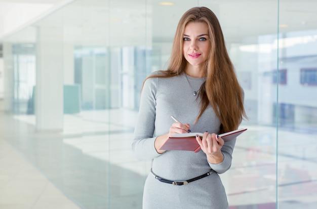 Femme affaires, tenue, journal intime, dans, elle, mains, et, regarder appareil-photo