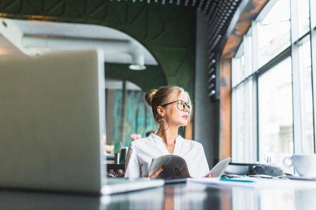 Femme affaires, tenue, journal, à, ordinateur portable, sur, bureau, dans, caf�