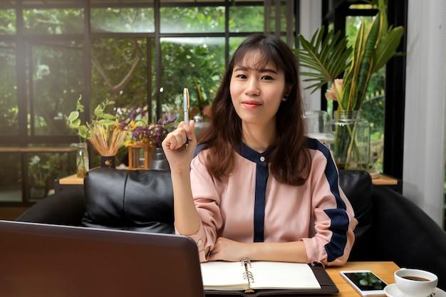 Femme affaires, tenue, a, stylo, et, séance, devant, ordinateur portable, dans, bureau personnel