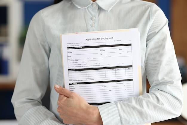La femme d'affaires tient le document d'emploi de formulaire de demande en mains