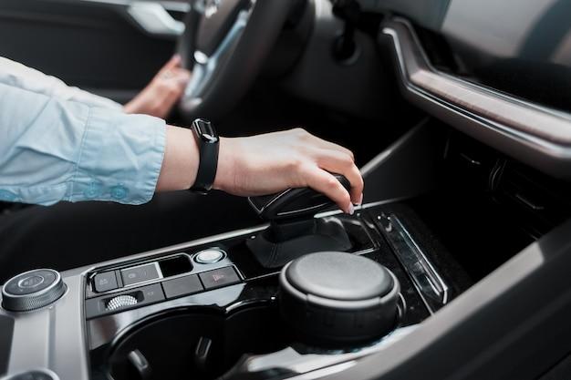 Femme d'affaires tient sa main sur la transmission automatique du sélecteur de vitesse