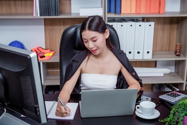 Femme d'affaires travaillant au bureau avec un sourire en position assise.