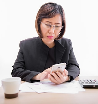 Femme d'affaires travaillant avec des documents et utiliser un smartphone au bureau