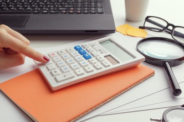 Femme d'affaires travaillant avec des données financières à la main à l'aide de la calculatrice