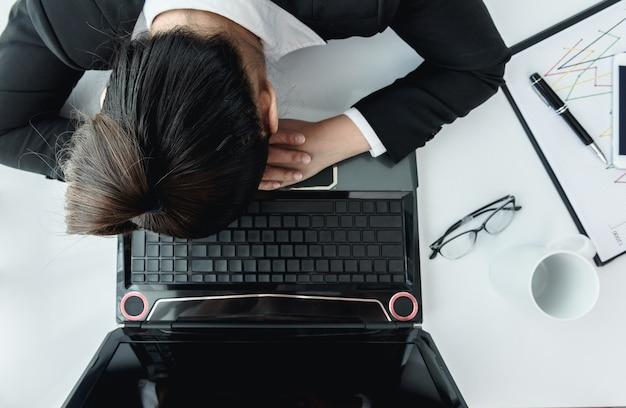 Femme d'affaires travaillant dur avec les dossiers de bureau et labtop. vue de dessus