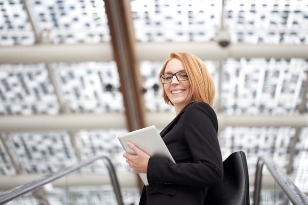 Femme d'affaires travaillant à l'extérieur de l'immeuble de bureaux avec des appareils numériques