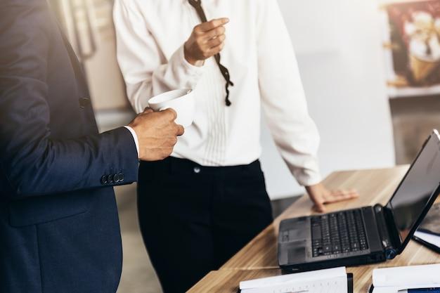 Femme d'affaires travaillant avec graphique d'entreprise et ordinateur portable et smartphone sur le dessus de la table