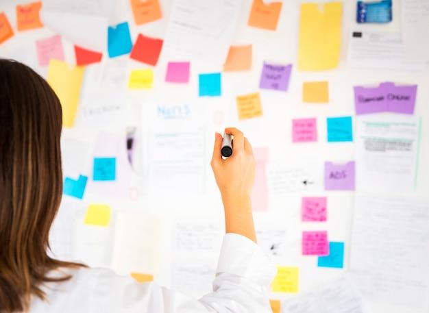Femme d'affaires travaillant avec des notes dans un bureau