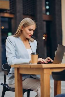 Femme d'affaires travaillant sur ordinateur dans un café et buvant du café