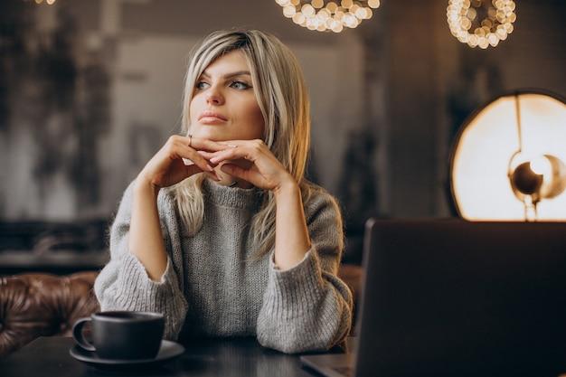 Femme d'affaires travaillant sur ordinateur dans un café