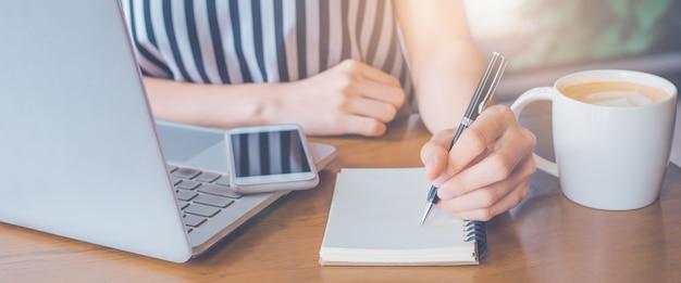 Femme d'affaires travaillant sur un ordinateur et écrivant sur un bloc-notes avec un stylo.