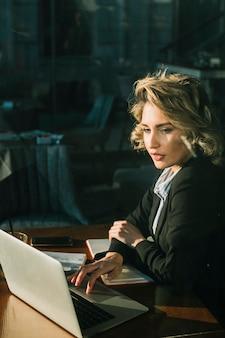 Femme d'affaires travaillant sur un ordinateur portable sur un bureau en bois