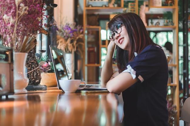 Femme d'affaires travaillant avec ordinateur portable et faire une note de quelque chose prendre des notes sur dans le café