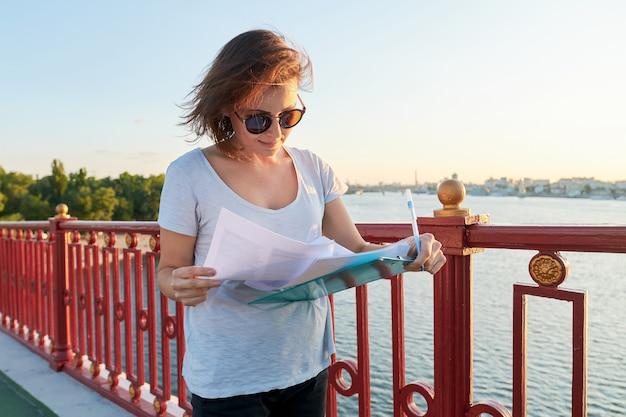Femme d'affaires travaillant en plein air, femme avec un document papier sur le presse-papiers, assistante sociale interrogeant des personnes dans la rue
