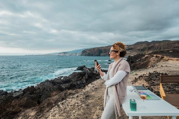 Femme d'affaires travaillant en plein air en toute liberté face à l'océan avec un ordinateur de bureau, un ordinateur portable et un téléphone portable