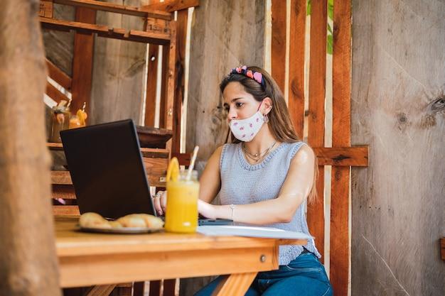 Une femme d'affaires travaillant sur son ordinateur portable tout en buvant du jus de fruits dans un bar.