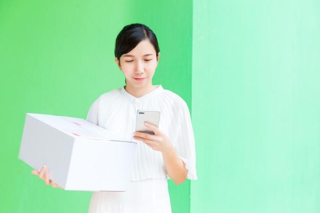 Femme d'affaires travaillant avec téléphone portable et boîte de colis shopping en ligne sur fond vert pastel.