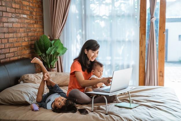Femme d'affaires travaillant tout en prenant soin des enfants