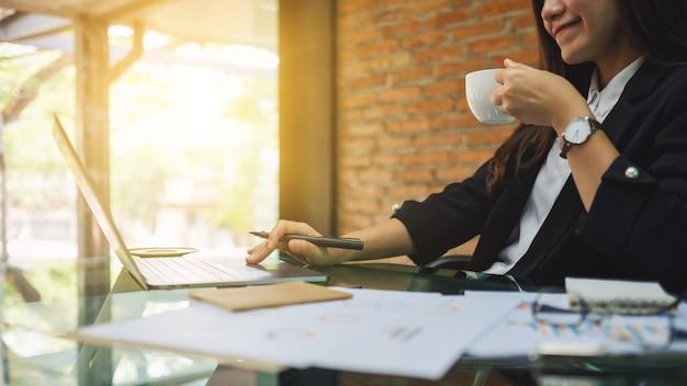 Femme d'affaires travaillant et utilisant un ordinateur portable tout en buvant du café au bureau