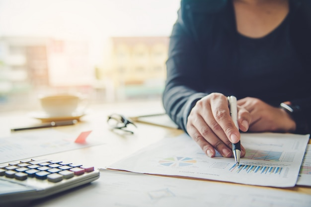 Femme d'affaires travaille sur des comptes en analyse commerciale avec des graphiques et de la documentation