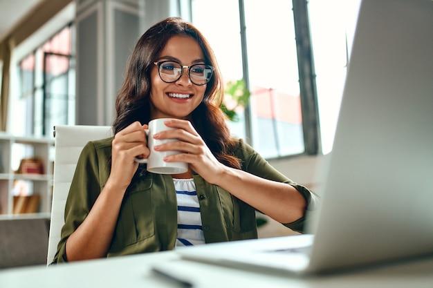 Une femme d'affaires travaille sur un ordinateur portable alors qu'elle est assise à une table à la maison et boit du café. indépendant, travail à domicile.