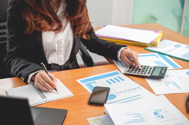 Femme d'affaires à travailler avec des rapports financiers et ordinateur portable au bureau