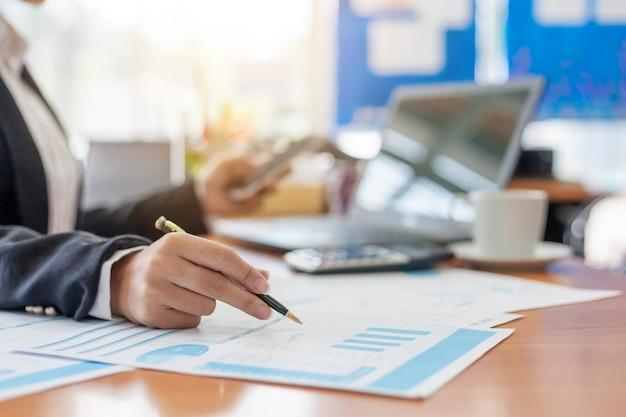 Femme d'affaires à travailler avec des rapports financiers