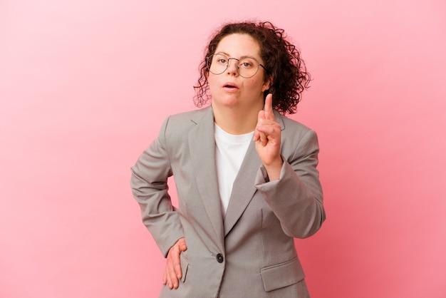 Femme d'affaires trisomique isolée sur un mur rose ayant une idée, un concept d'inspiration.