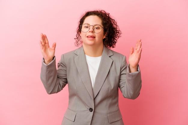 Femme d'affaires trisomique isolée sur un mur rose recevant une agréable surprise, excitée et levant les mains.