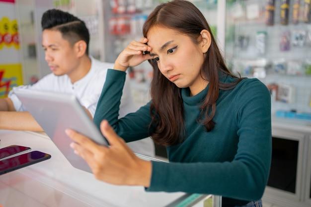 Une femme d'affaires triste confrontée à des problèmes lors de l'utilisation d'une tablette à côté d'un homme