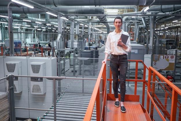 Femme d'affaires en usine de menuiserie industrielle - production de planches en bois avec des machines modernes