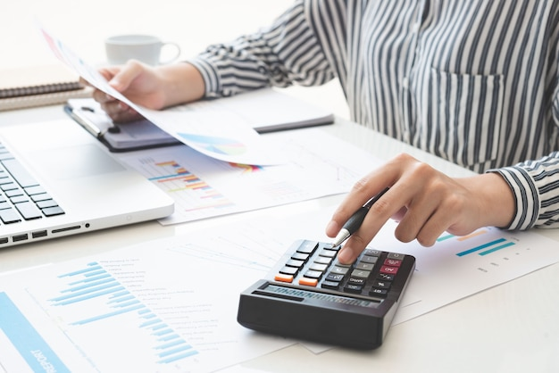 Une femme d'affaires utilisant une calculatrice et écrivant prend note avec calculer. impôts et concepts économiques.