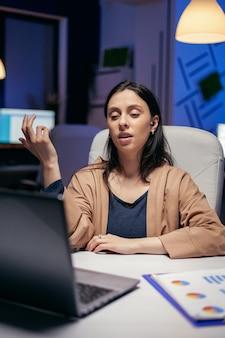 Femme d'affaires utilisant des écouteurs au cours d'un appel en ligne faisant des heures supplémentaires. femme travaillant dans la finance lors d'une vidéoconférence avec des collègues la nuit au bureau.