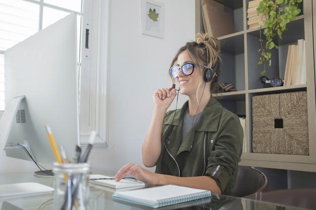 Femme d'affaires utilisant un ordinateur de bureau tout en participant à une vidéoconférence parlant au casque avec micro à la maison. jeune femme travaillant sur ordinateur avec un sourire.