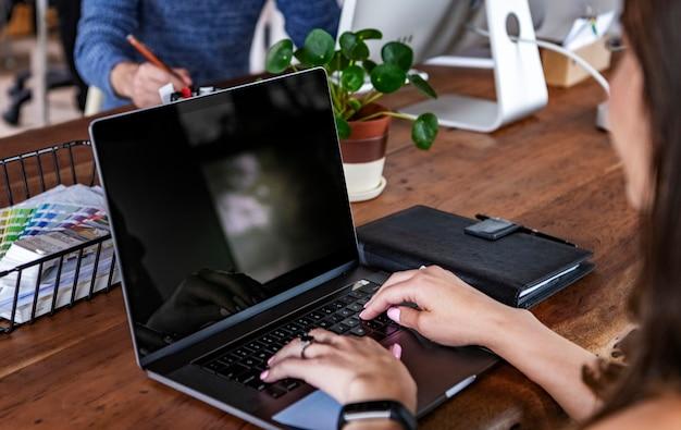 Femme d'affaires utilisant un ordinateur portable lors d'une réunion