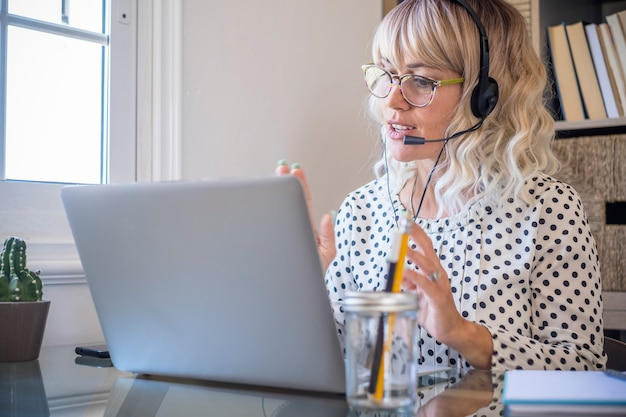 Femme d'affaires utilisant un ordinateur portable tout en parlant au casque avec micro à la maison jeune femme confiante