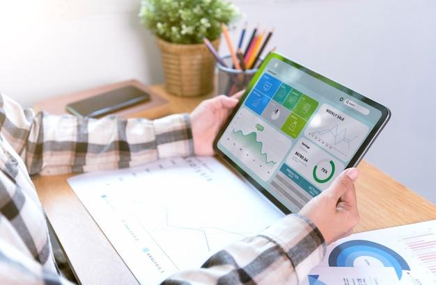 Femme d'affaires utilisant une tablette pour analyser le concept de réussite des statistiques de stratégie financière de l'entreprise et la planification de l'avenir dans la salle de bureau.