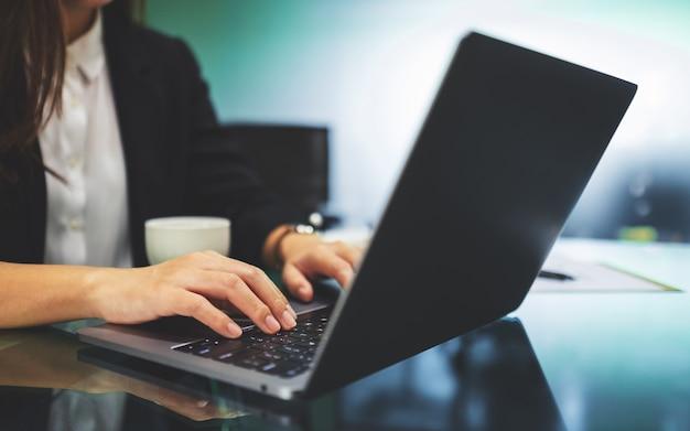 Une femme d'affaires en utilisant et en tapant sur le clavier de l'ordinateur portable tout en travaillant au bureau