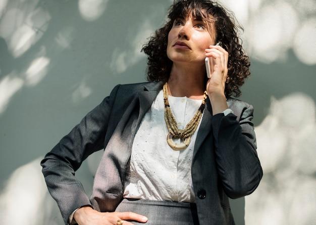Femme d'affaires utilisant la technologie de communication par téléphone mobile