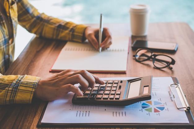 Femme affaires, utilisation, calculatrice, à, analyse, diagrammes, et, graphiques, rapport affaires, et, écriture, sur, cahier, dans, bureau